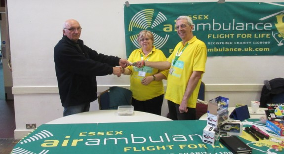 Dave G4UVJ presenting the raffle fund to Carole and Clive from Essex Air Ambulance