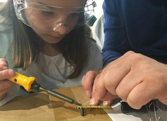 Kathryn carefully soldering capacitors